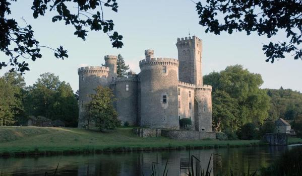 Idyllic French castle with towers and battlements, surrounded by a moat