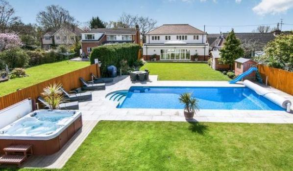An immaculate garden with a sky blue swimming pool and Jacuzzi