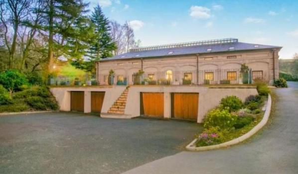 Converted waterworks with sweeping driveway and six car garage