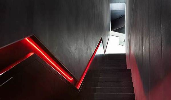 Black staircase with a sunken handrail lit with red LEDs