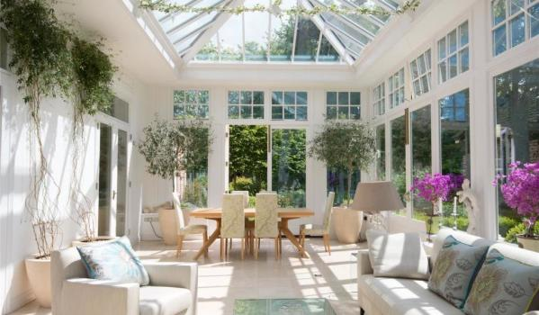 A large conservatory with dining table and sofas