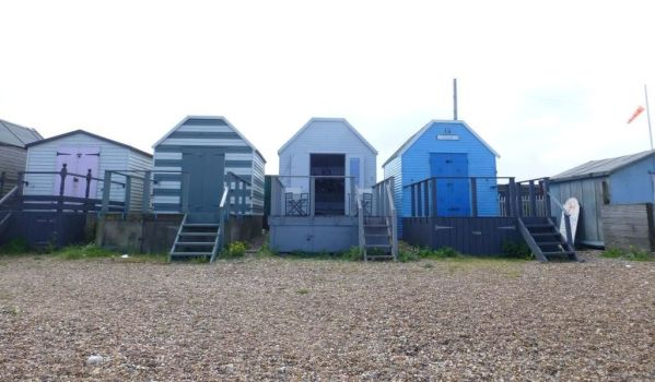 Grey beach hut on the pebbled beach at Whitstable Harbour