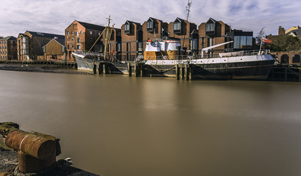 River Hull at high tide and beached obsolete fishing vessel.