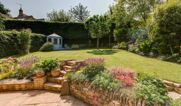 Beautiful sunlit garden with flower beds, a lawn and a summer house