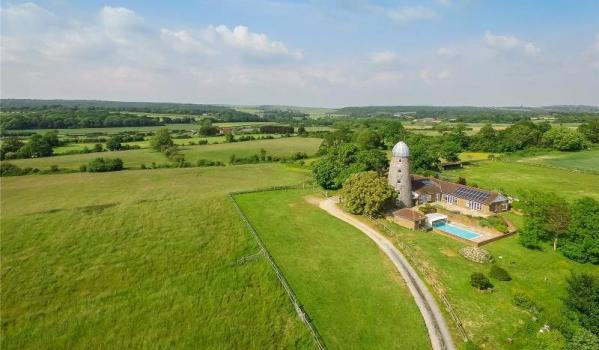 A converted windmill with an outdoor swimming pool