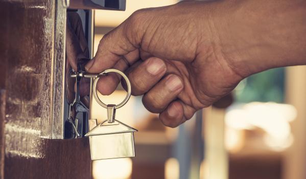 Hand with keys locking a door