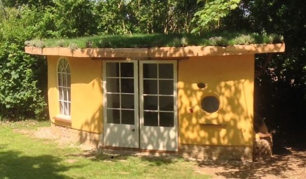 Yellow cob-built shed with a turf roof