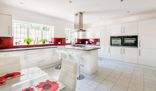 Huge white kitchen with red splashbacks