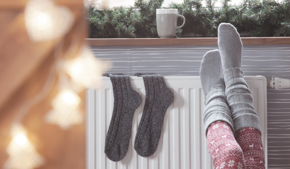 Feet warming on a radiator in winter