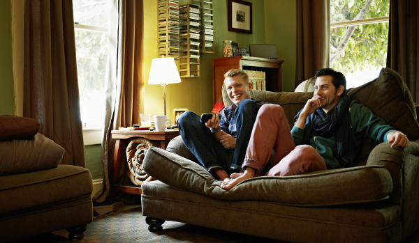 Young men relaxing on sofa at home