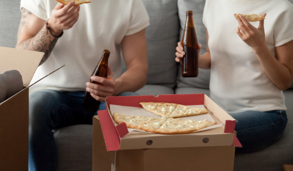 Couple eating pizza on moving boxes