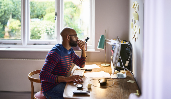 Man looking at articles on desk computer