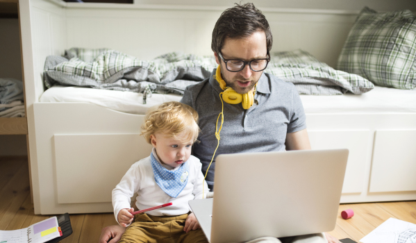 Dad and son at laptop - Getty Images