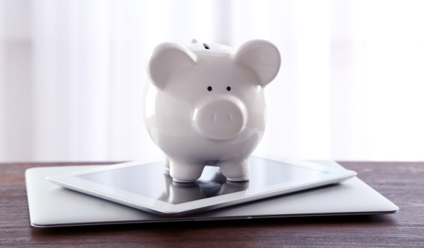 Piggy bank on top of tablet and laptop